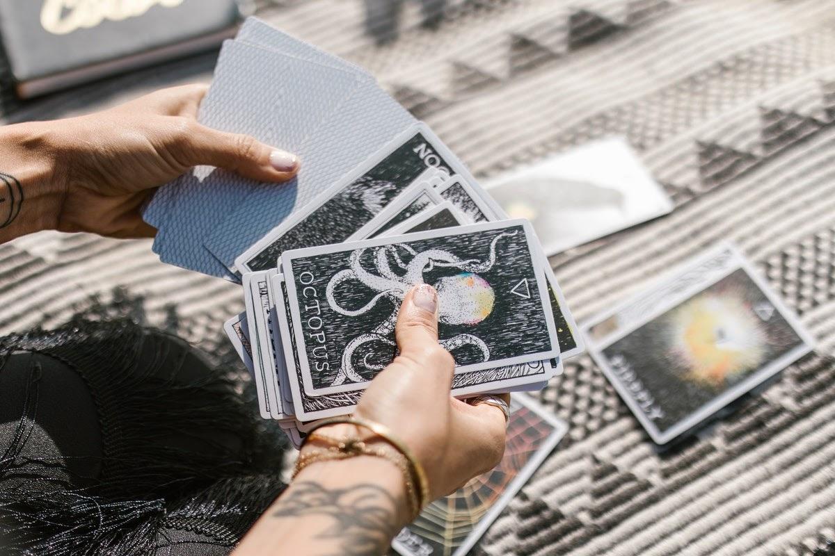 Tattooed hands holding a deck of tarot cards.
