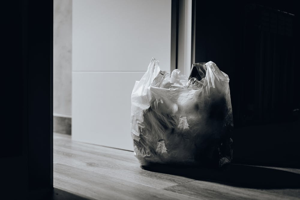 a plastic bag filled with other plastic bags sits in front of a dimly lit doorway.