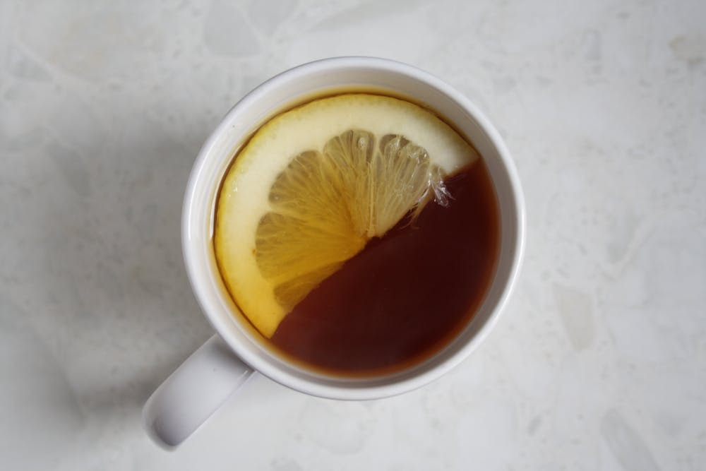 A hot cup of tea is placed against a white background and showcases half of a sliced lemon placed on top of the tea.