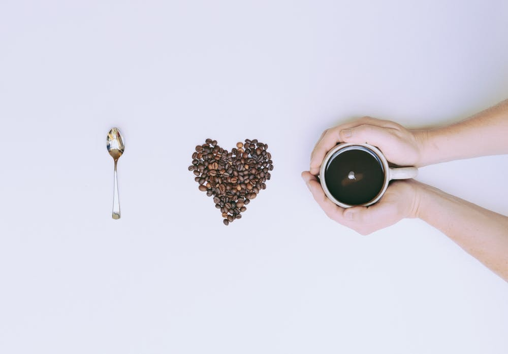 """a spoon, coffee beans, and two hands holding a cup of coffee spell out """"I love coffee""""."""