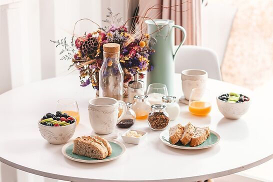 A white table with bread, fruit, and orange juice next to a pot of flowers.