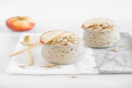 Two small cups of oatmeal with apple slices on top.