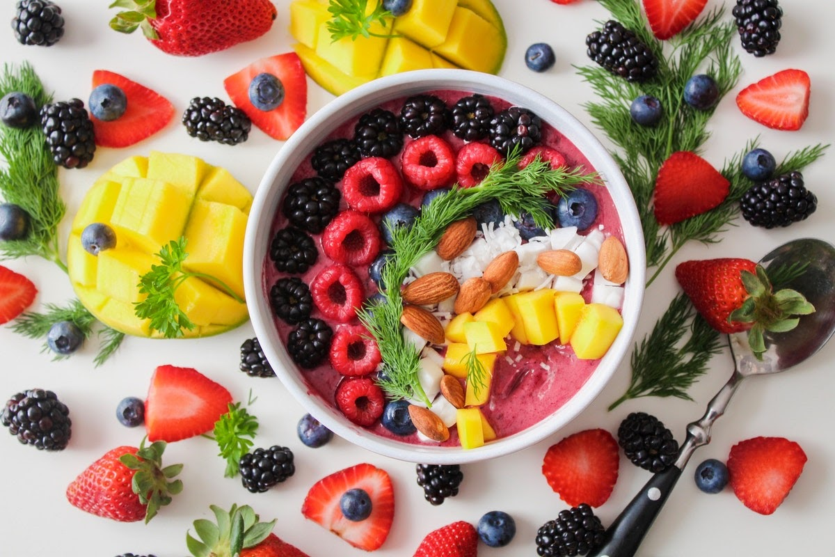 A colorful array of fruit on top of a ink smoothie bowl surrounded by fruit.