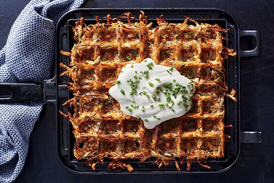 A crispy waffle shaped hash brown topped with sour cream.