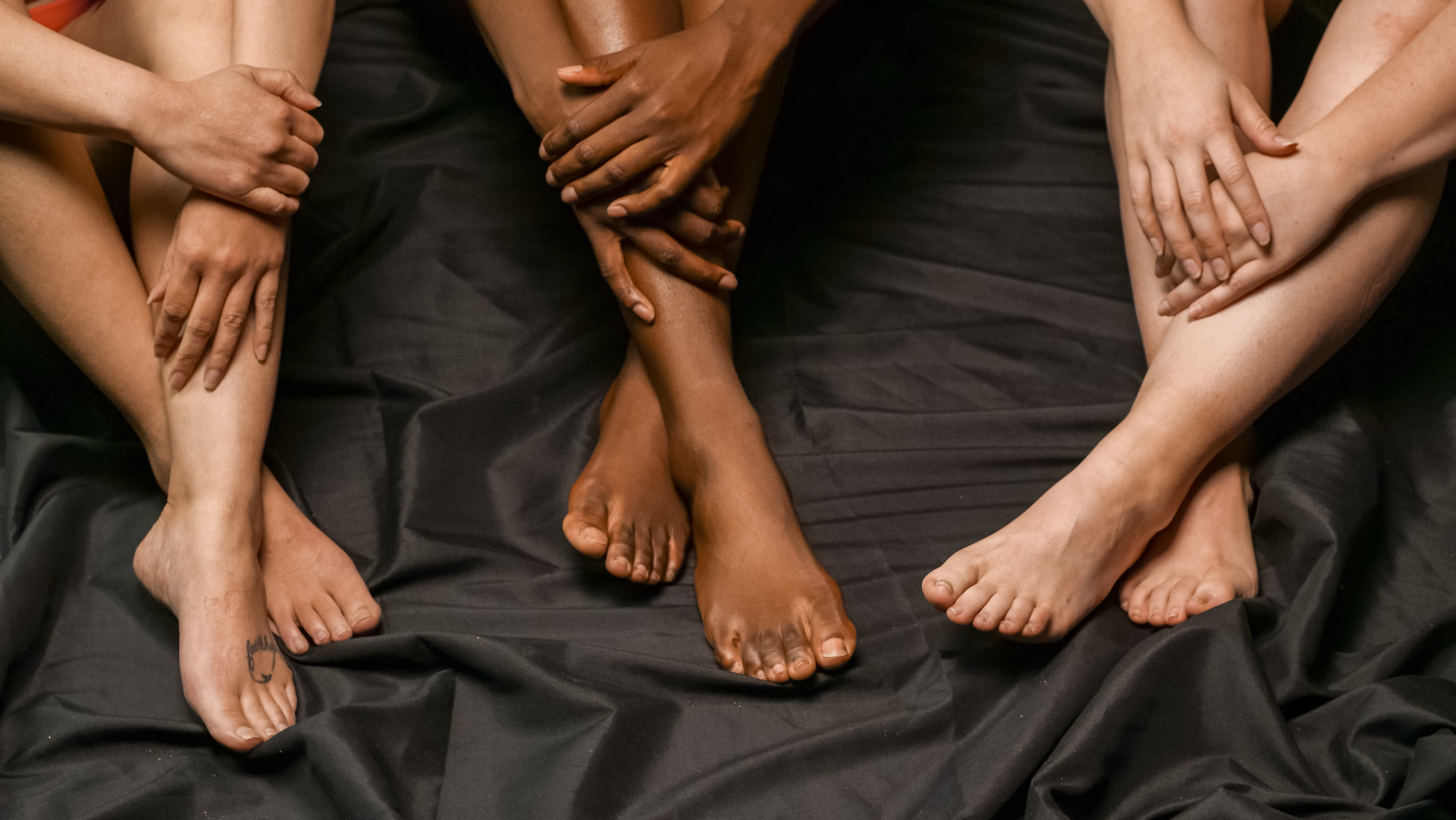 Three people are sitting on a black silk sheet with their feet crossed and their hands on wrapped around their knees.