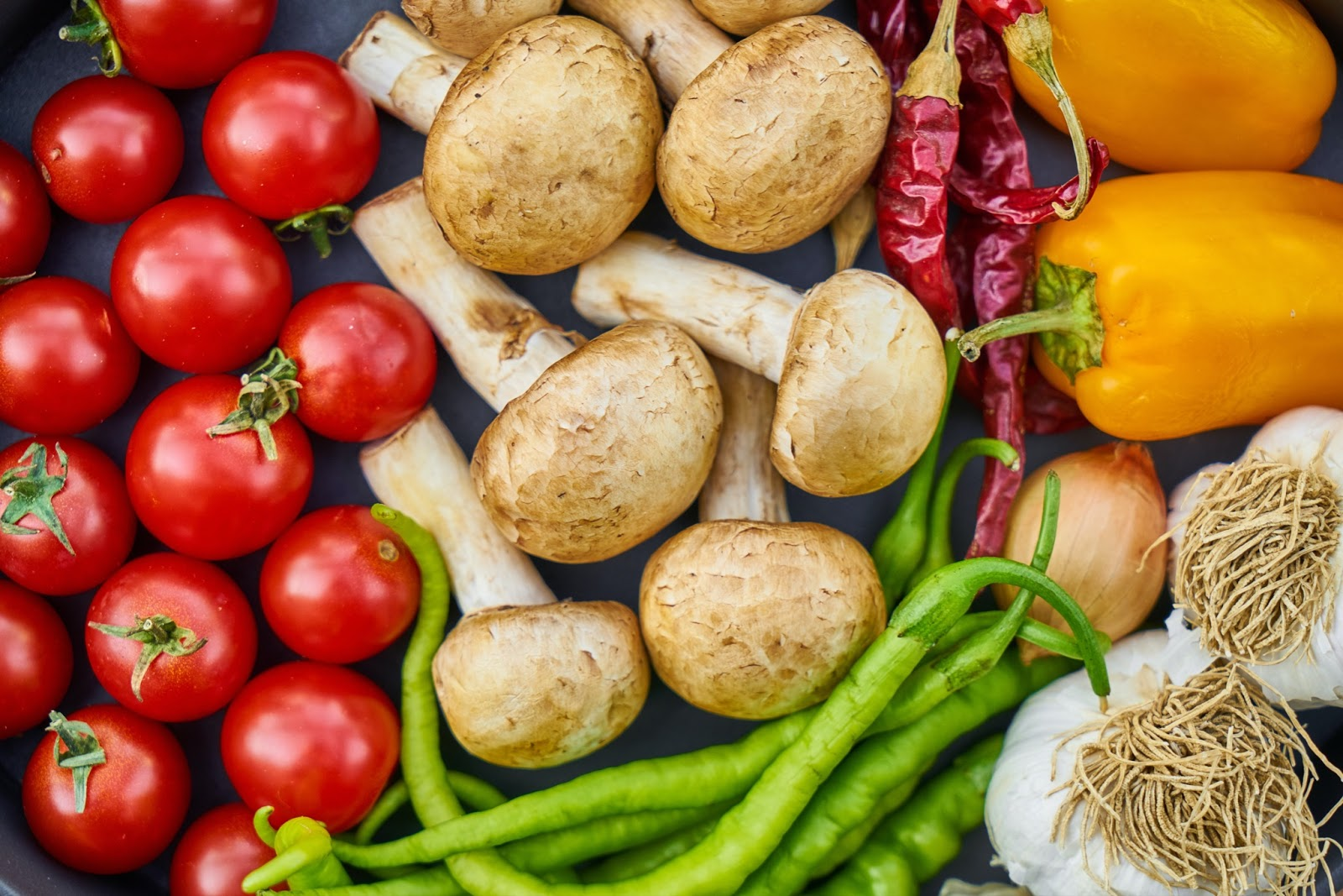 tomatoes, mushrooms, peas, peppers, chilis, and garlic fill the photo as they are placed on a table.