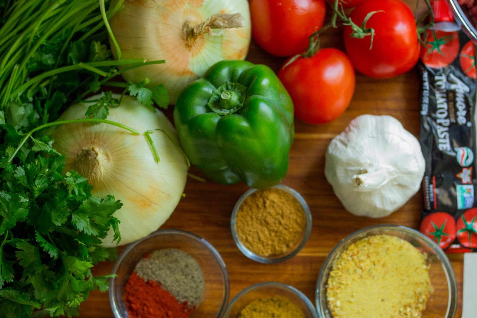 A colorful array of vegetables and spices fill a table.
