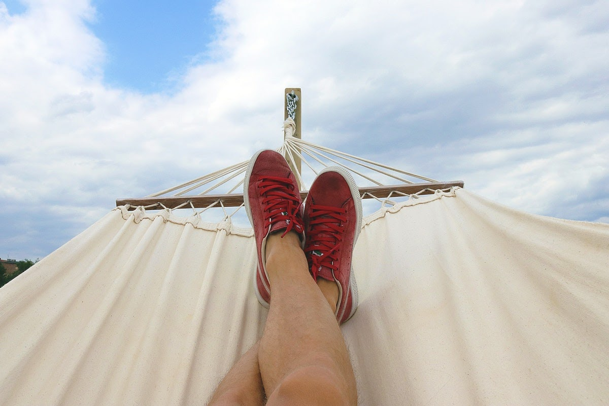 A person in red sneakers lying on a hammock.