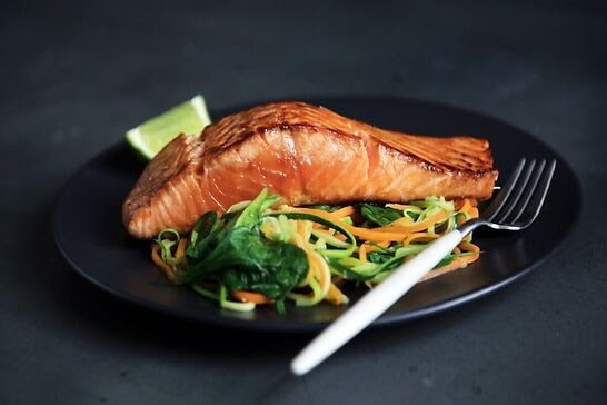 Realistic looking lab made salmon on a plate of greens.