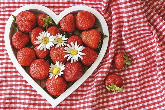 A heart-shaped bowl of strawberries.