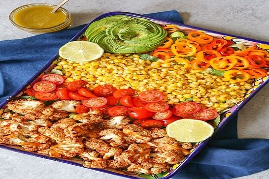 A platter filled with cauliflower, tomatoes, corn, peppers, and avocado.