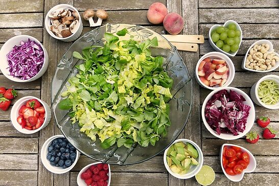 Salad ingredients all in different bowls around a large bowl of lettuce.