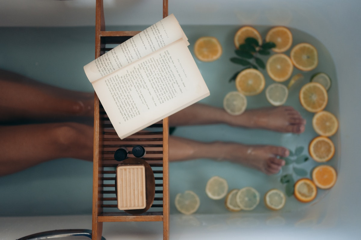 A woman in a bathtub filled with a few sliced lemons and limes and a book, a bar of soap, and sunglasses on a shelf.