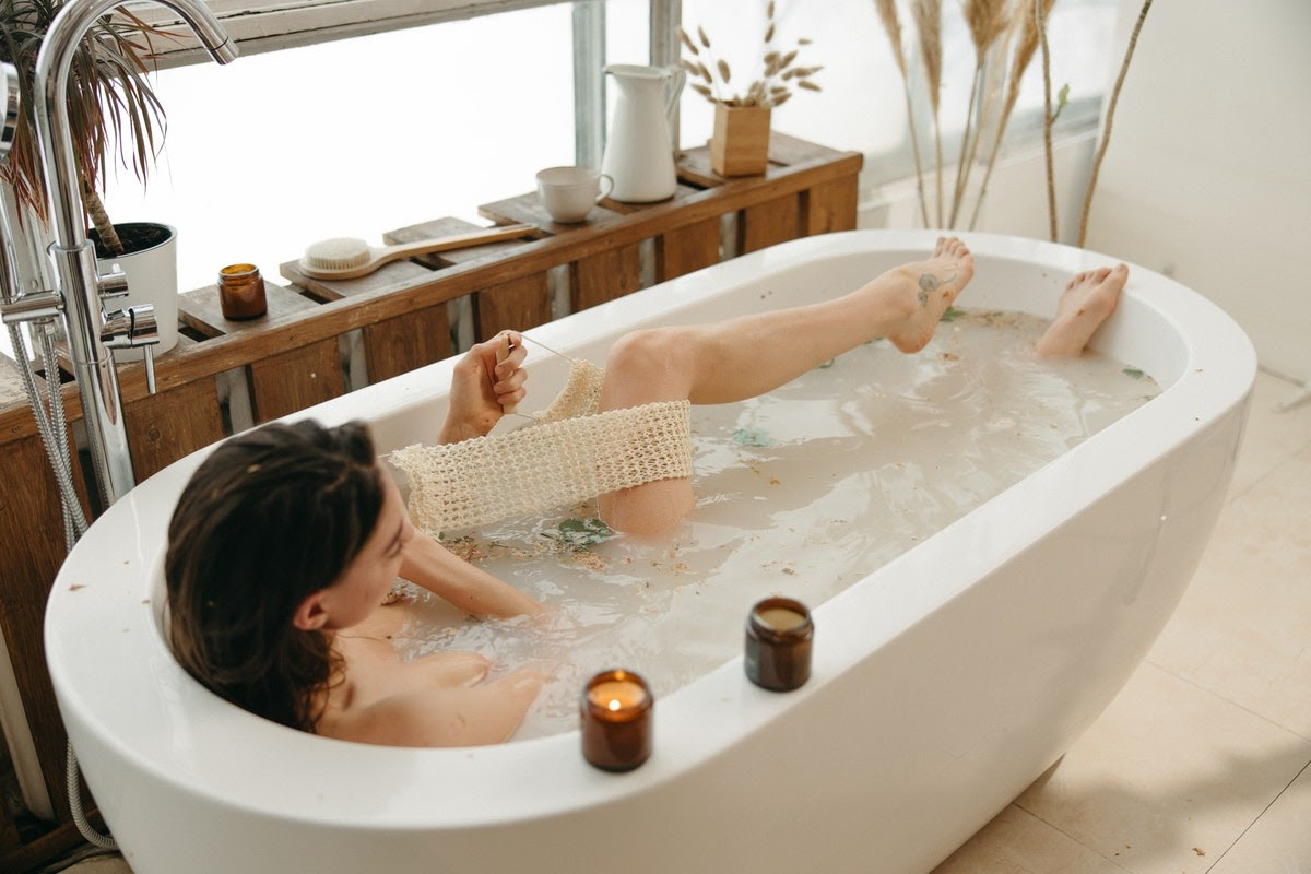 A woman in a bath scrubbing with a loofah next to two candles.