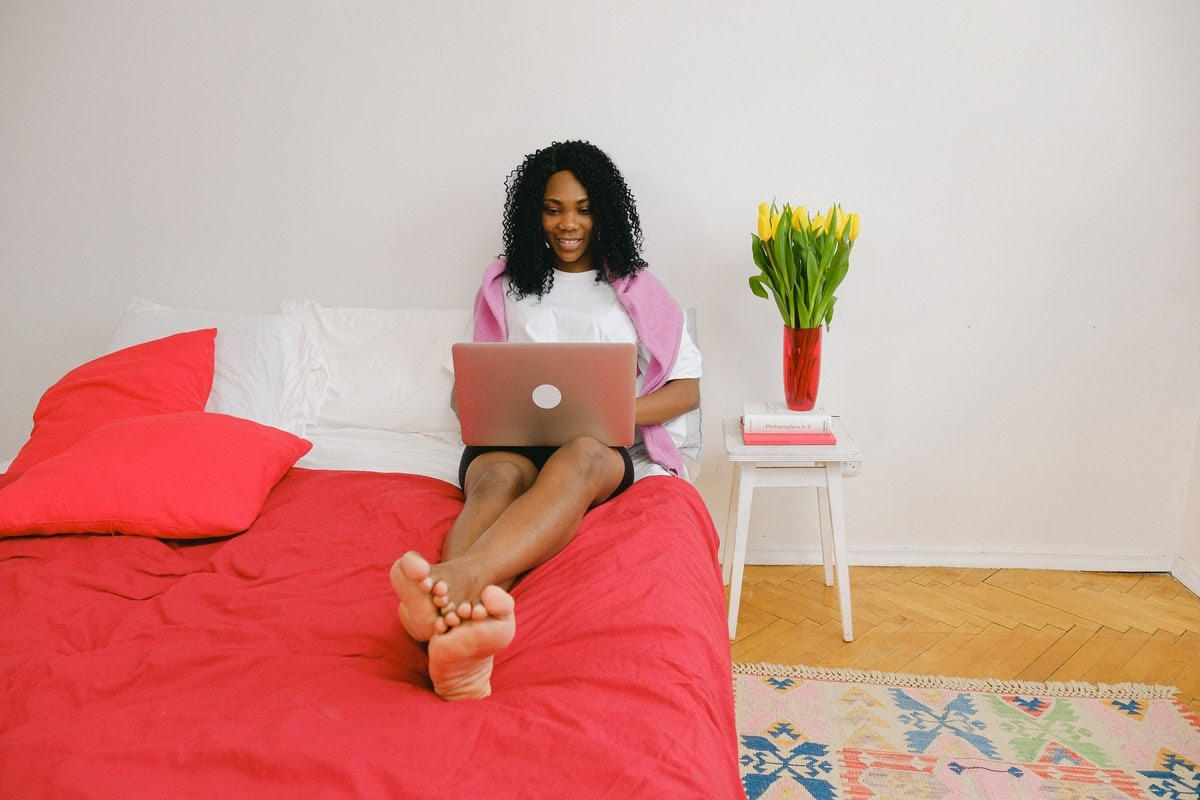 A woman on her bed using a laptop while smiling.