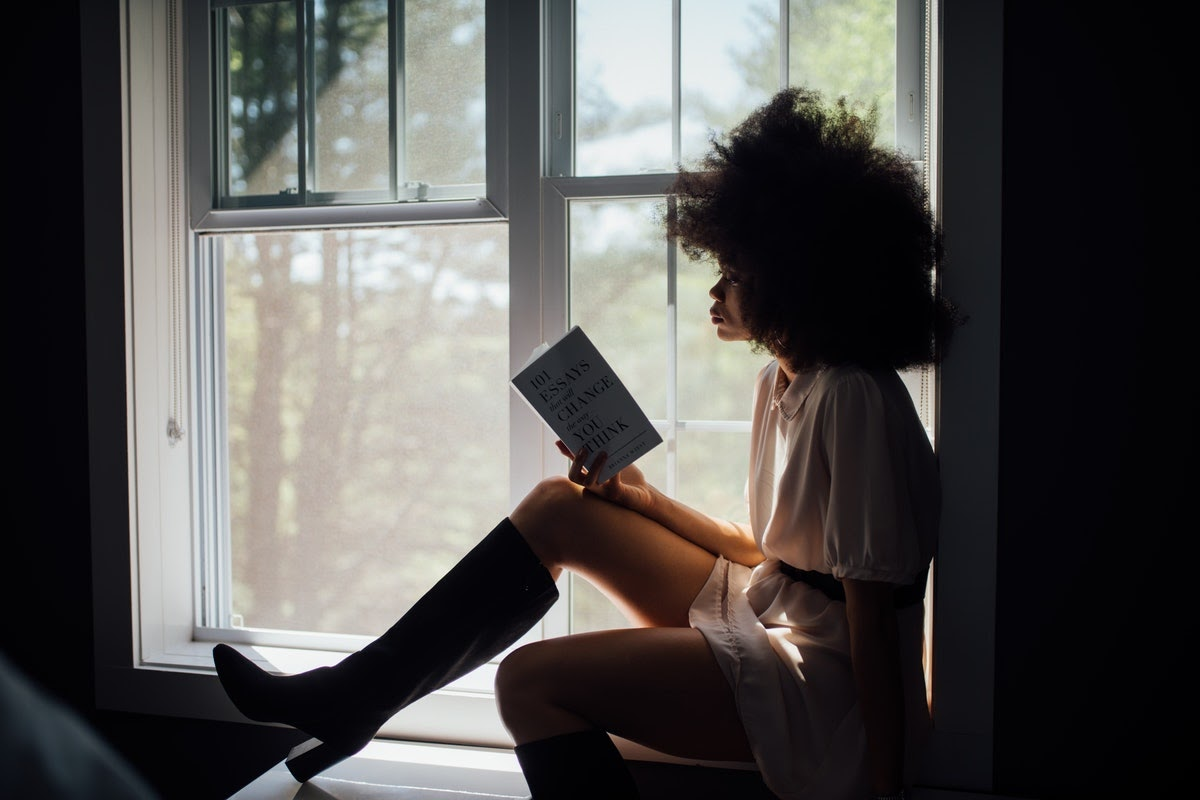 A woman reading a book on a windowsill.