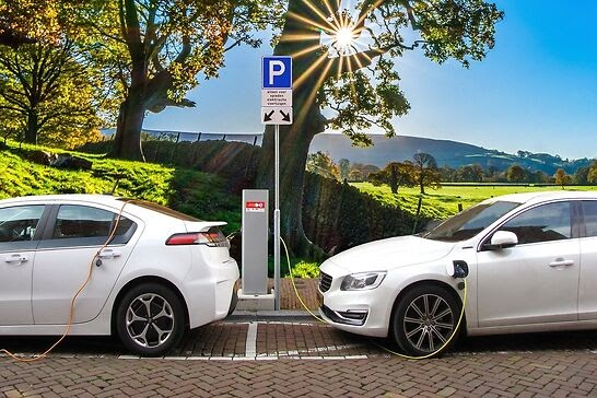 Two electric cars charging next to each other.