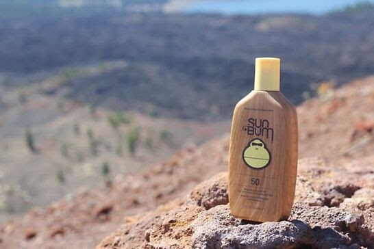 A brown bottle with a yellow monkey face on a rocky mountainside.