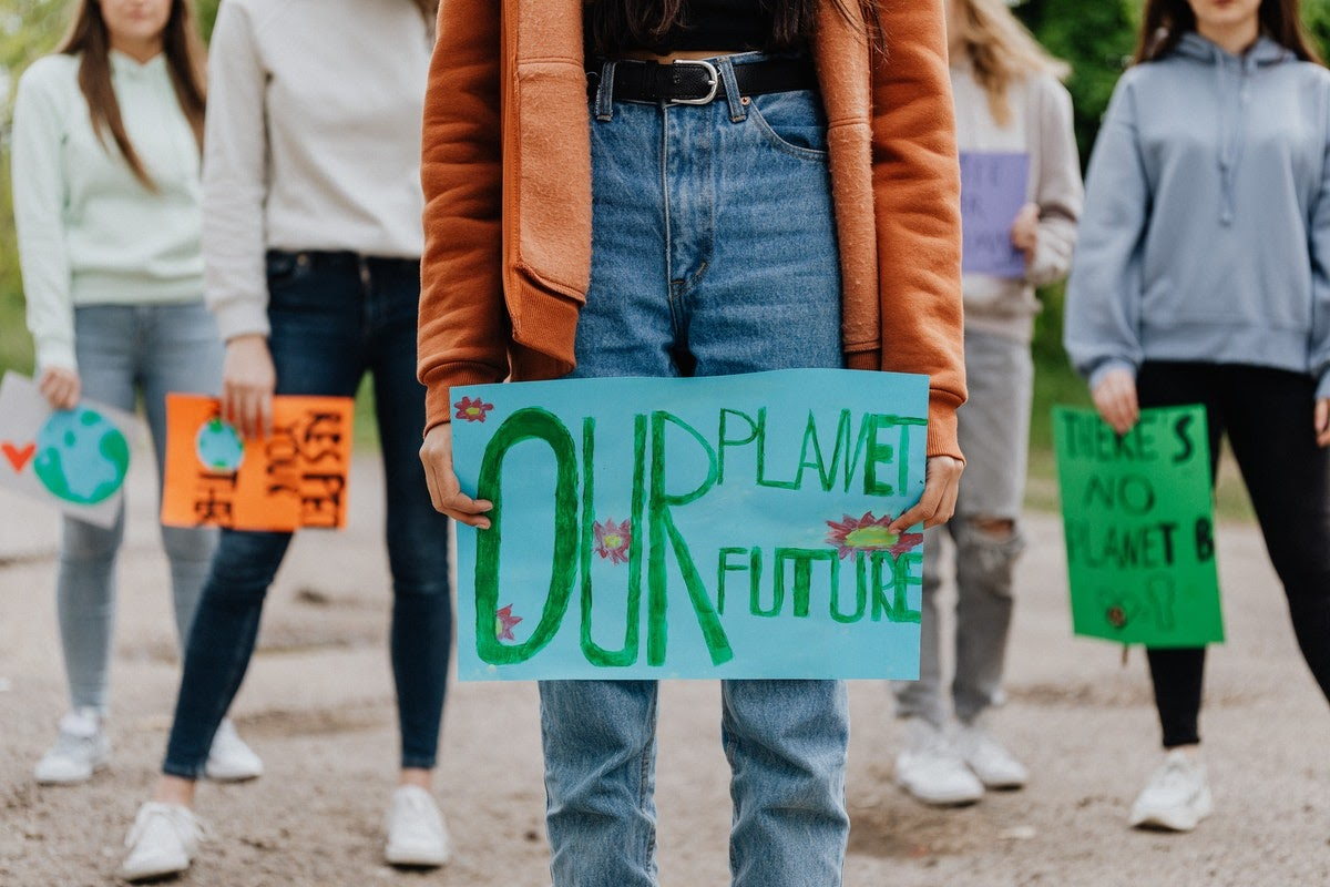 People with signs protesting to stop climate change.