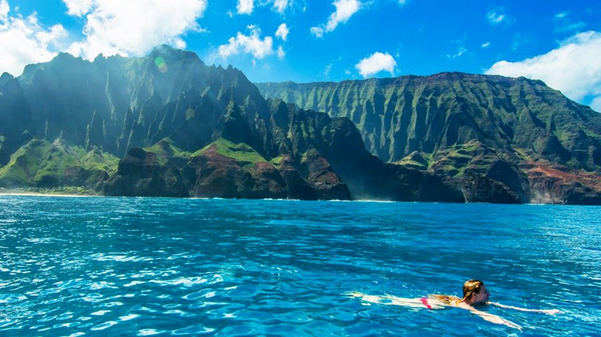 Soaking up the sun in the crystal clear waters of Na Pali coast. Take a boat ride to explore the surreal coast of Kauai. Image courtesy of misstraveltheworld.com.