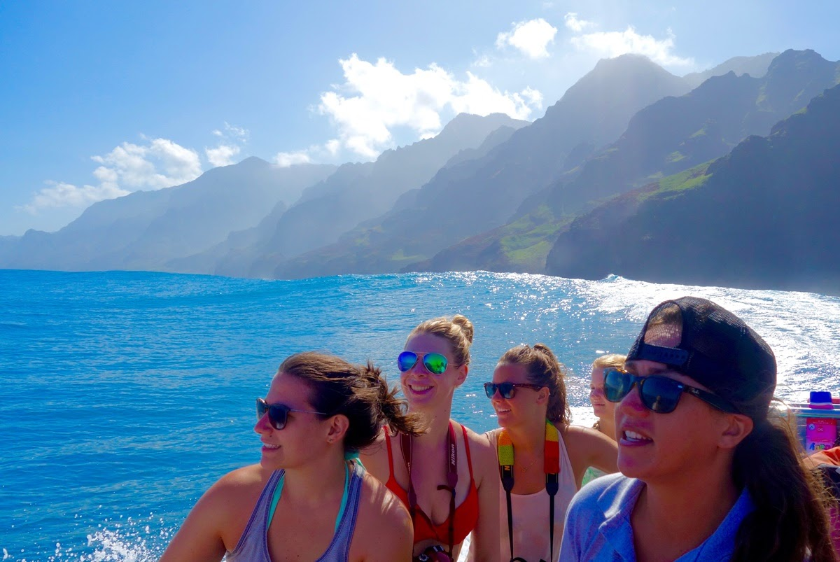 Exploring the shallow blue waters near the coastline by boat. Travelers exploring the Na Pali coast by sea pictured caught off guard by a whale sighting from afar. Image courtesy of misstraveltheworld.com.