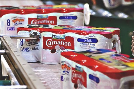 Nestlé's production line of Carnation Evaporated Milk. Nestlé is a Swiss multinational food and drink processing corporation headquartered in Vevey, Vaud, Switzerland. Since 2014, Nestlè has become the largest food company in the world. Image courtesy of takepart.com.