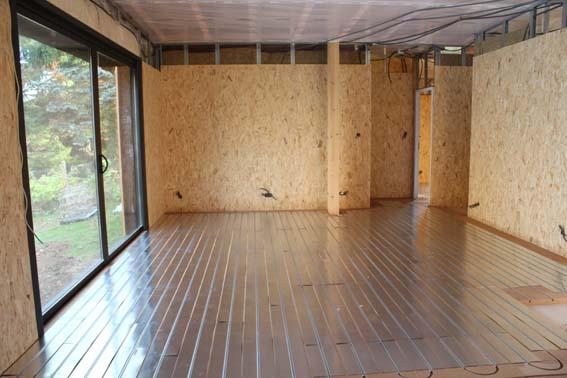 Plancher chauffant mince en cours de pose dans une maison ossature bois