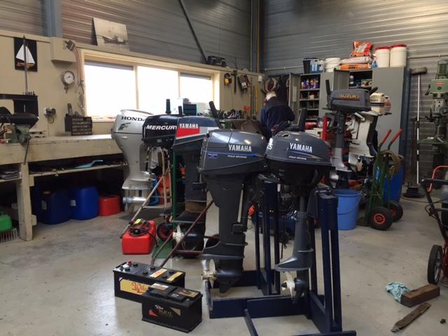 foto van verschillende merken buitenboordmotoren op een rij in de werkplaats van Hulzinga Watersport