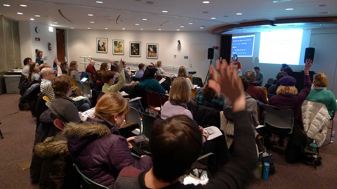 Photo of CCAC Workshop. People seated in front of a presentation, some with hands raised.