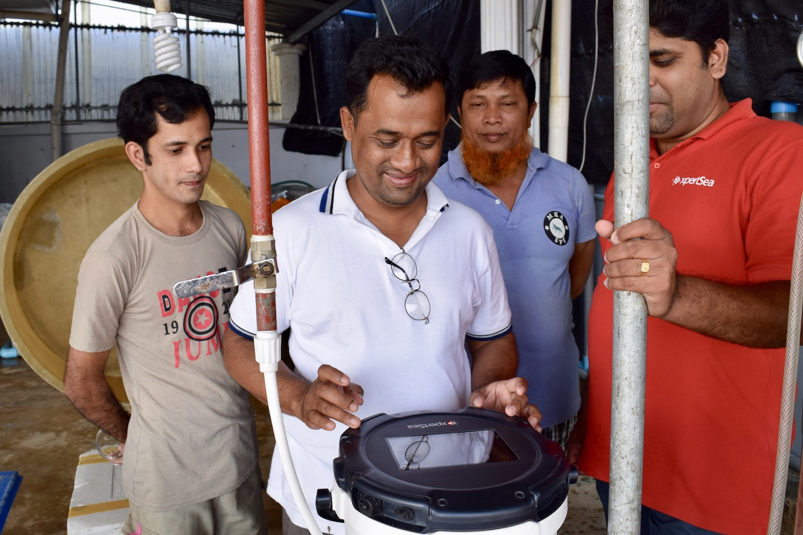 Employees using the Xpercount to count bagda in a Bangladesh shrimp hatchery