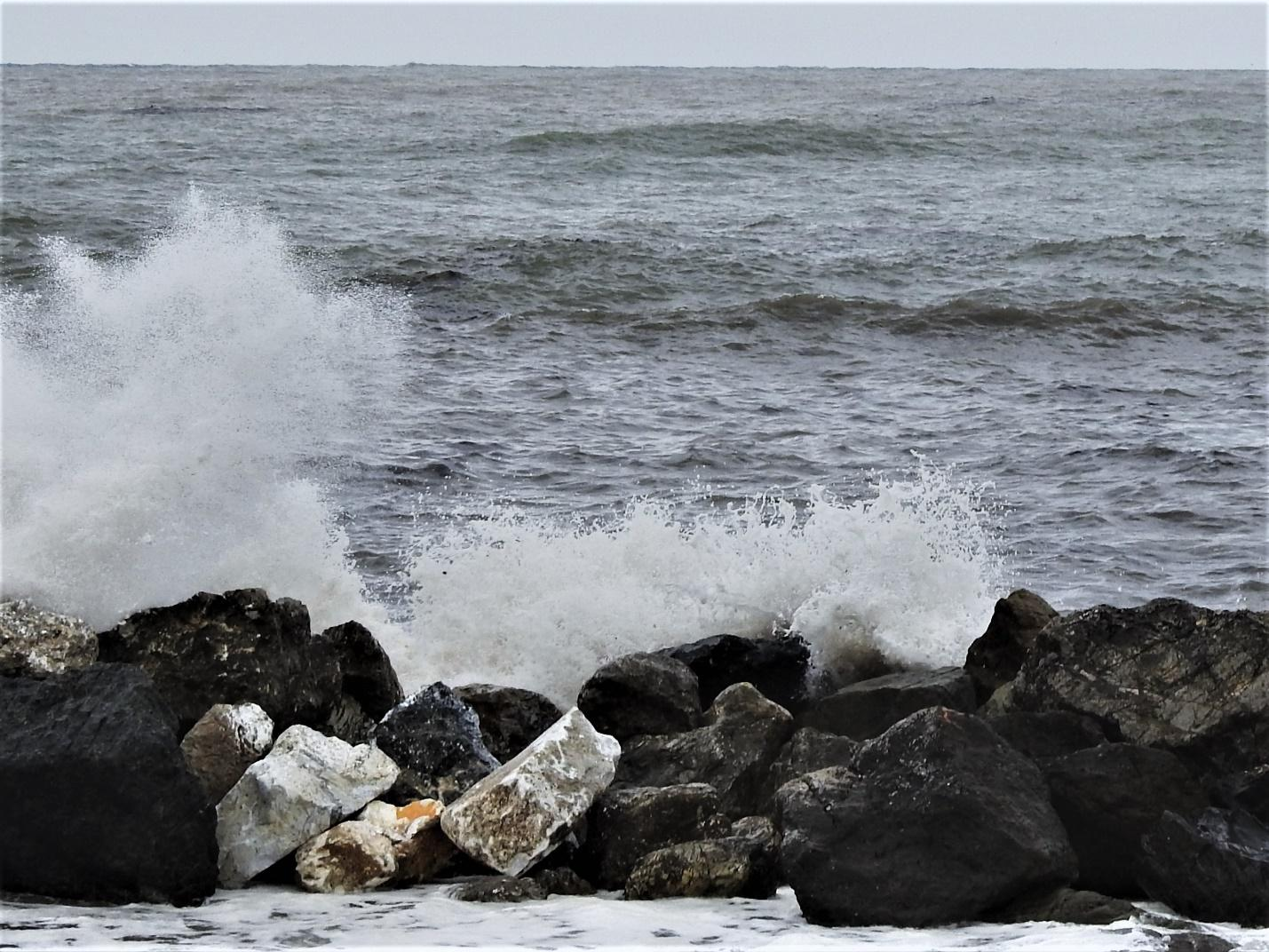 A rocky beach next to the oceanDescription generated with very high confidence