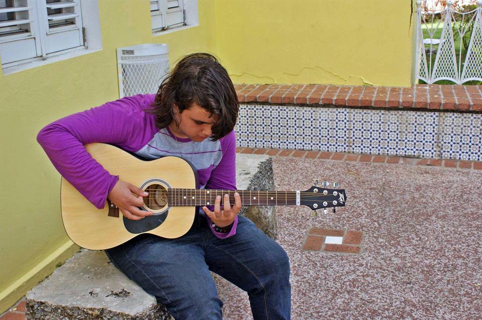 Joven tocando guittara en la Escuela de Bellas Artes de Carolina, Puerto Rico.