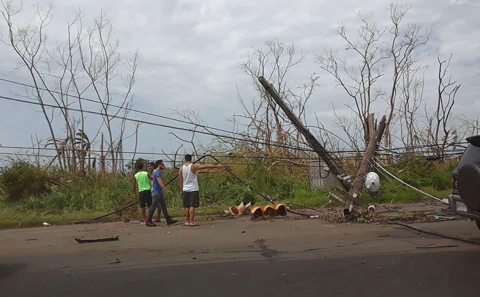 Jóvenes en la Avenida Iturregui de Carolina observando postes y cablería tirada en la carretera por el Huracán María.