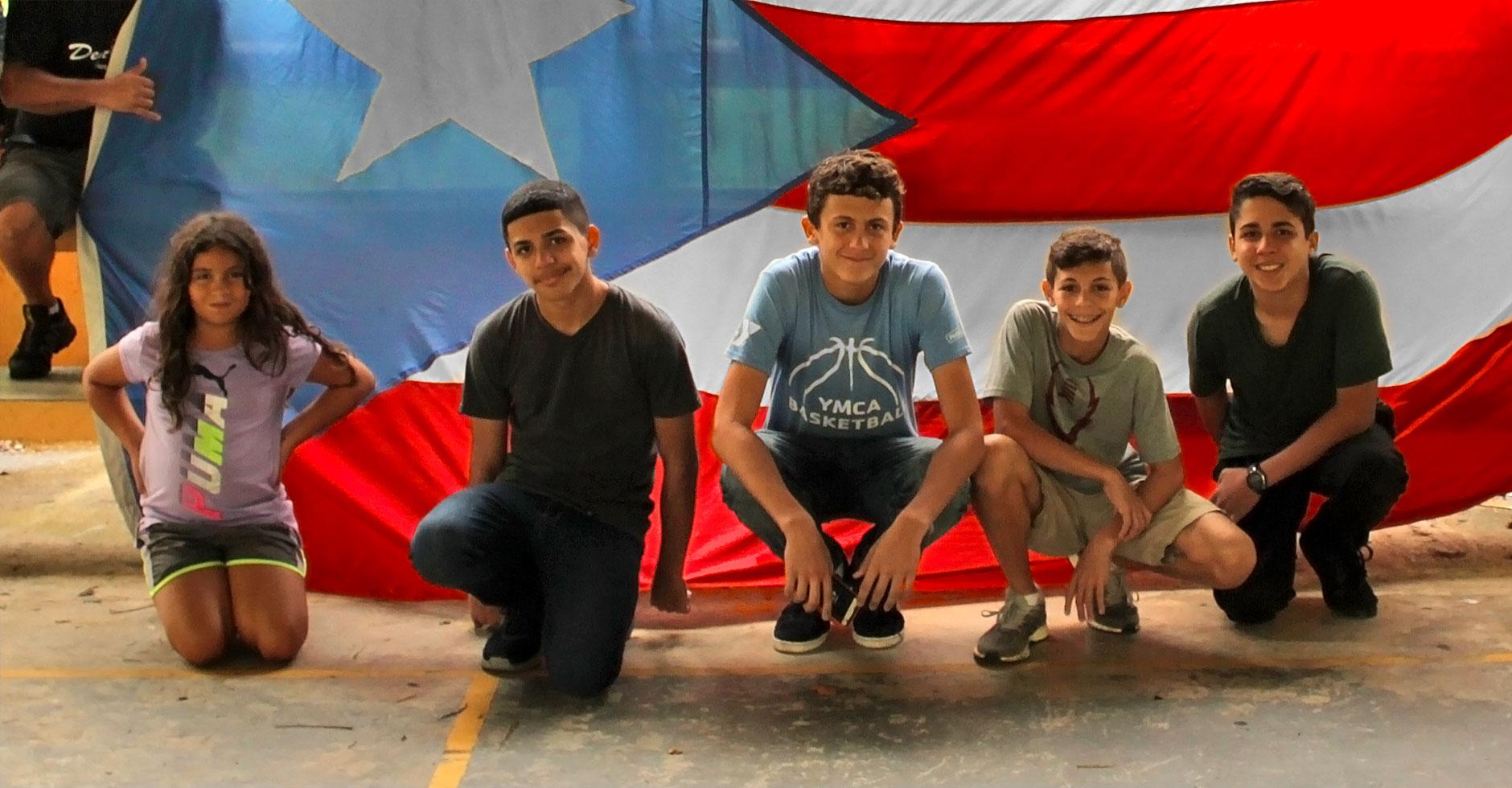 Niños con la bandera de Puerto Rico de fondo.