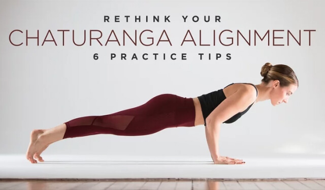 Woman practicing low yogic push-up (chaturanga dandasana) with unconventional alignment in front of a white wall
