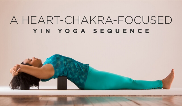Woman practicing supported fish pose over yoga blocks to stimulate her heart chakra