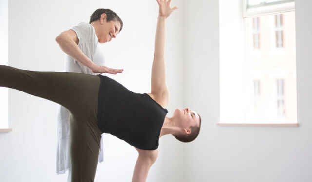 Yoga teacher assisting a student in half moon pose (ardha chandrasana)