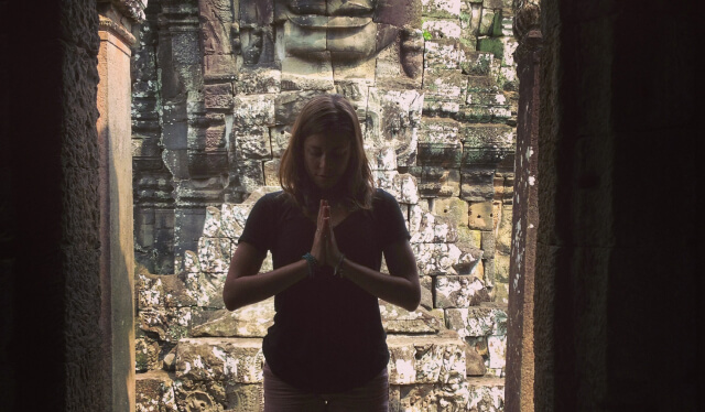 Silhouetted yoga teacher with her hands at her heart in namaste at the Temples of Angkor in Siem Reap, Cambodia
