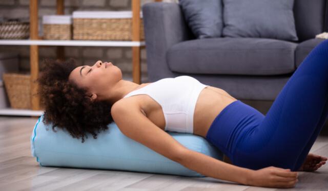 Woman practicing restorative yoga over a yoga bolster