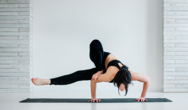 Woman practicing yoga arm balance