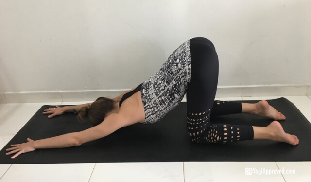 Woman practicing puppy pose (anahatasana) to relieve back pain