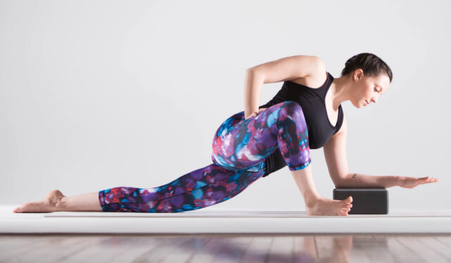 Woman practicing twisted lizard pose with a white background
