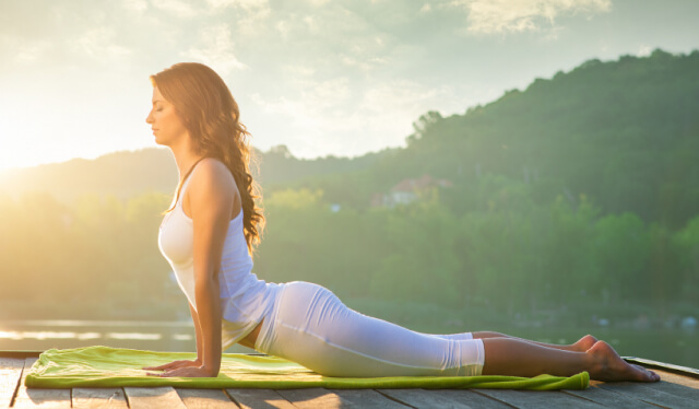 Woman practicing upward facing dog in front of mountains