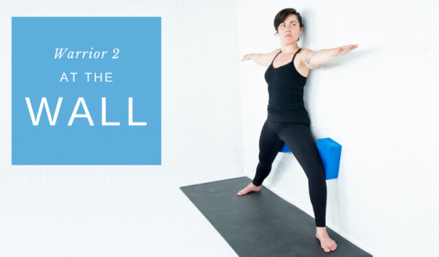 Woman practicing Warrior II at the wall with yoga props