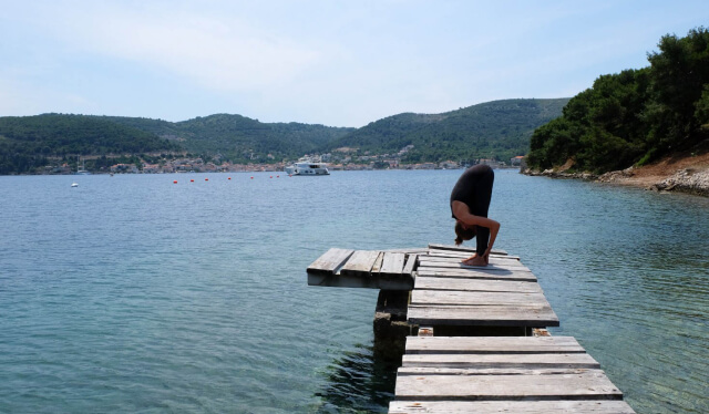 Woman practicing standing forward fold (uttanasana) on a dock surrounded by the sea