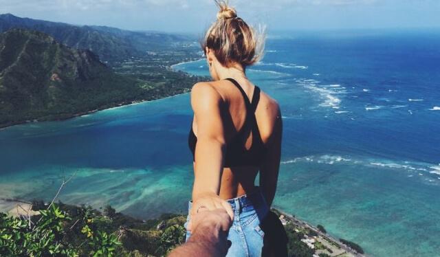 Woman pulling someone else's hand behind her walking toward a beautiful ocean scene