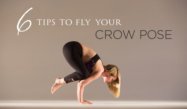 Woman practicing crow pose (bakasana) against a beige backdrop