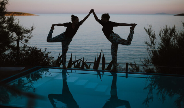 Two woman in silhouettes practicing dancer's pose (natarajasana) in front of a pool with the sea behind them