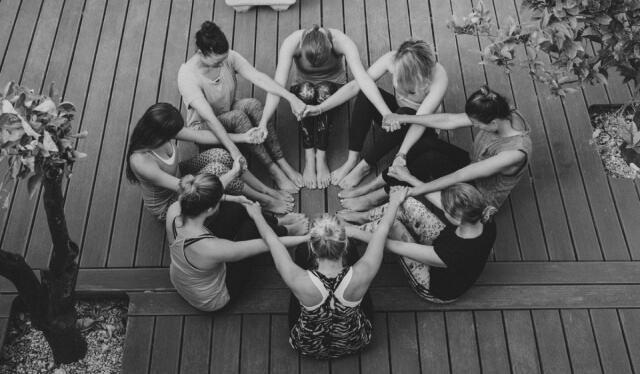 Group of yogis holding hands and creating a mandala with their bodies