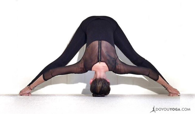 Woman practicing a wide-legged standing forward fold (prasarita padottanasana) in front of white wall